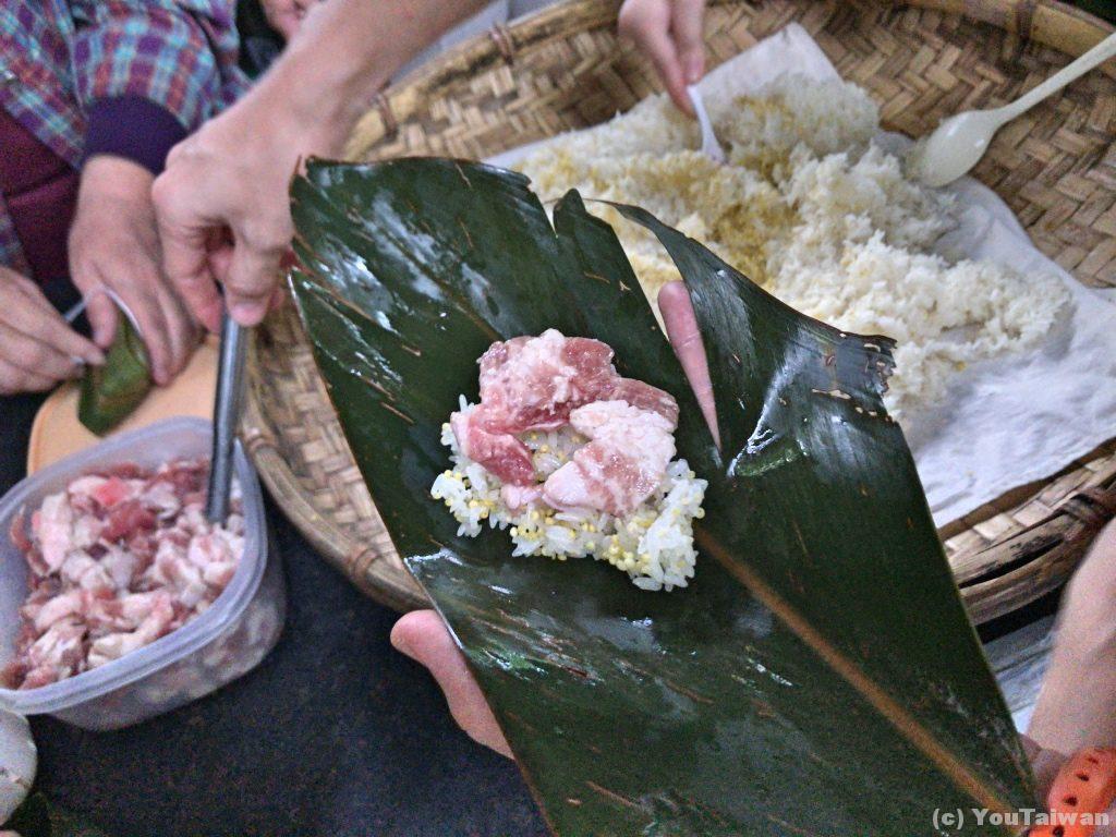 ヤシの葉の上に蒸し米を敷く