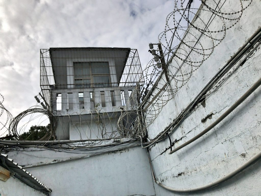 厳重に鉄条網が張られた監獄の壁と監視塔